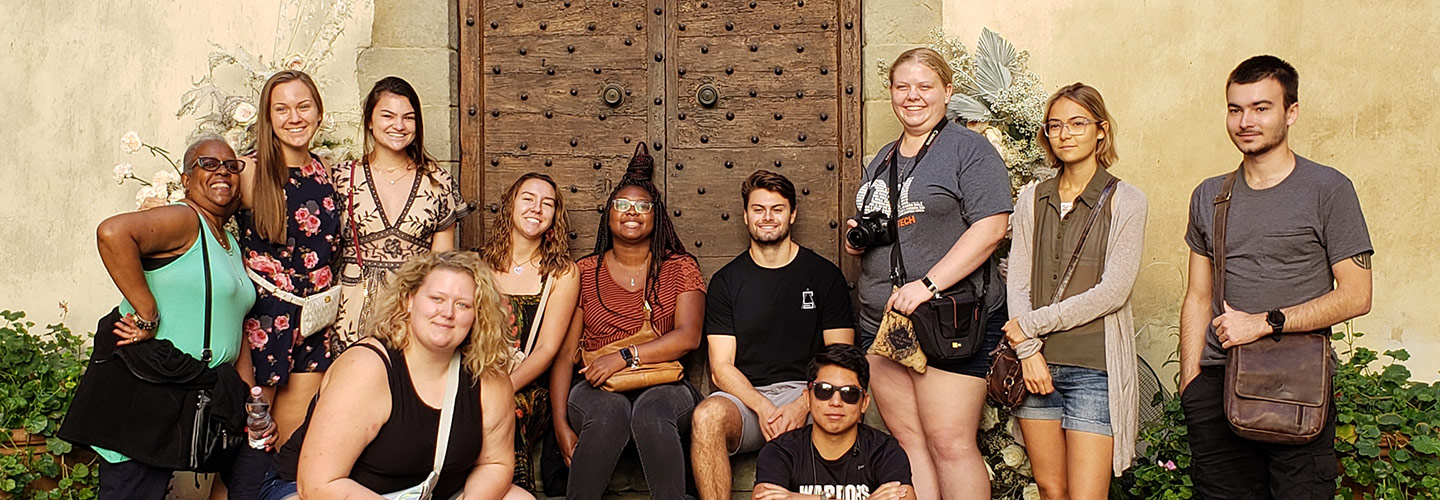Indiana Tech students and faculty grouped together in front of an aged door in Florence, Italy