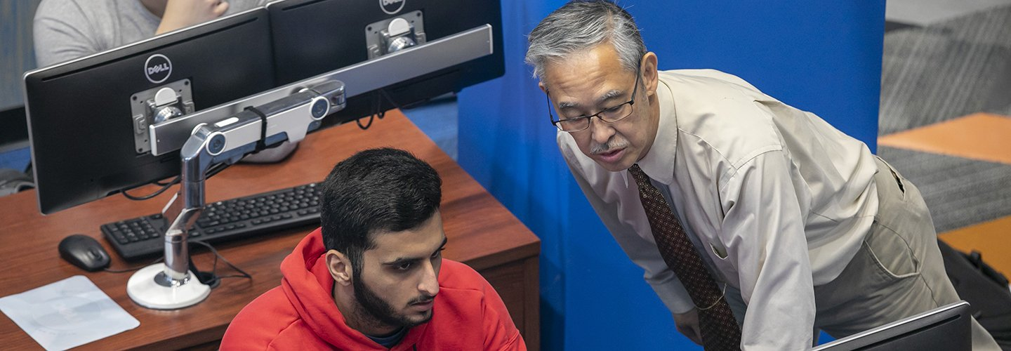 Professor Darryl Togashi discusses a problem during a cybersecurity class.